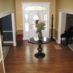 After picture of painted entryway, dining room and living room. We also consulted on paint colors, furniture design, hand made rugs, custom drapery, and lighting